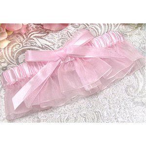 Light Pink Bridal Garter . $8.99. This lovely LIGHT PINK bridal garter makes a wonderful addition to your wedding or your prom. This light pink bridal garter is made of satin on top with sheer fabric on the bottom, and finished with a satin and sheer bow on the front of the garter, for a simply classic look.  This light pink bridal garter is available in 1 standard size, and is is packaged in a white box with a clear, see-through lid.