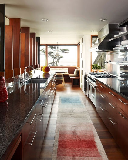 Houzz Tour: Wood and Wonder in a Modern Carmel Residence | The galley kitchen continues the simplicity of materials — wood and, instead of steel, granite tops that are nevertheless dark like the steel details. The line of the kitchen ends in the breakfast area (no formal dining area is included), which looks to the ocean.