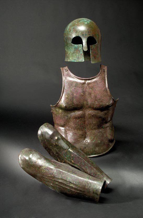 Greek set of armour: a Corinthian helmet, 7th century B.C., a muscle armour breastplate, 5th century B.C. and a pair of greaves, 5th century B.C.E.