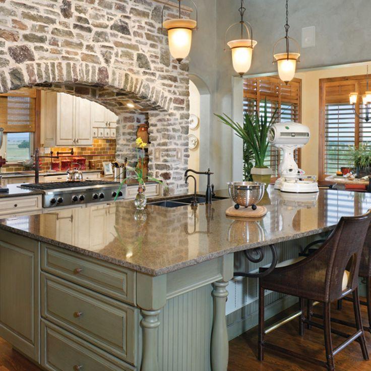 Rustic Kitchen With Brick Arch And Double-sided Stove