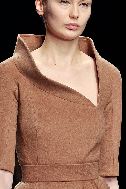 This stand collar is very loose at the top and sags down in certain areas to create a relaxed but still very clean look. The fabric looks like a wool as it's able to make the collar stand like it does.