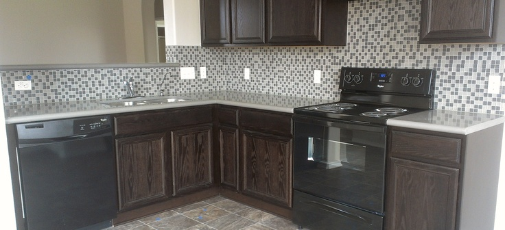 Waterleaf addition in Kyle Texas. Small glass block back splash with dark cabinets and appliances.