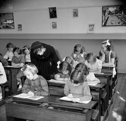 1947. Afbeelding van een groep leerlingen en een toekijkende Zuster Augustinesse in een klaslokaal op de Piusschool voor R.K. onderwijs voor meisjes (Oudegracht 33) te Utrecht.  N.B. Het onderwijs op de school werd verzorgd door de Zusters Augustinessen van St.-Monica (Klooster Genazzano, Waterstraat 2).