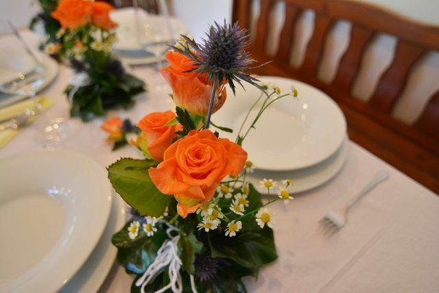Oranžová varianta výzdoby svatební tabule. Použitý materiál: růže, eryngium, heřmáken, zeleň.