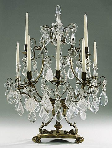 "Pair of Girandoles 1730 ""Drops of rock crystal or glass were often included in lighting fixtures because they multiplied and fragmented the candlelight. At the court of Louis XIV at Versailles, candelabra were often placed on tall stands to throw the light farther around the room. A Parisian newspaper, the Mercure Galant, reported in 1677 about people's astonishment at the amount of light created as the candle flames reflected off the crystal."""