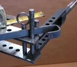Homemade metal bender constructed from flat steel bar stock and steel rods.