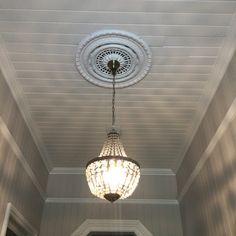 Pressed metal ceiling rose over crystal basket chandelier in entrance foyer