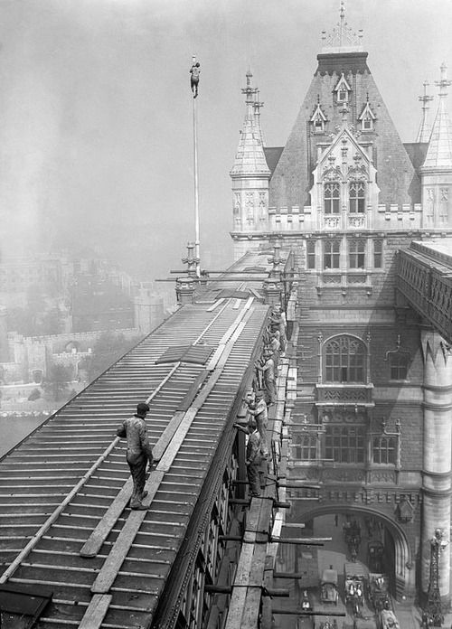 A workman on one of the gantry ways high above Tower Bridge. London, 1913