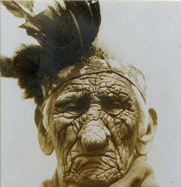 the man on the picture (Indian Ka-Nah-Be-Owey Wence, or shortened John Smith) was really 129 years old, and the oldest living person at the time who lived in three centuries. It is mentioned that he lived from 1791 to 1920.