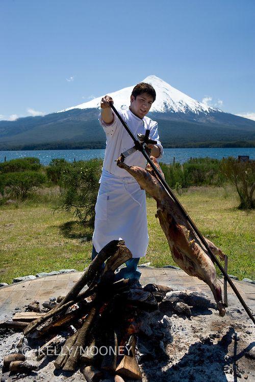 Chef roasting lamb, Lake Llanquihue and Osorno Volcano, Chile..