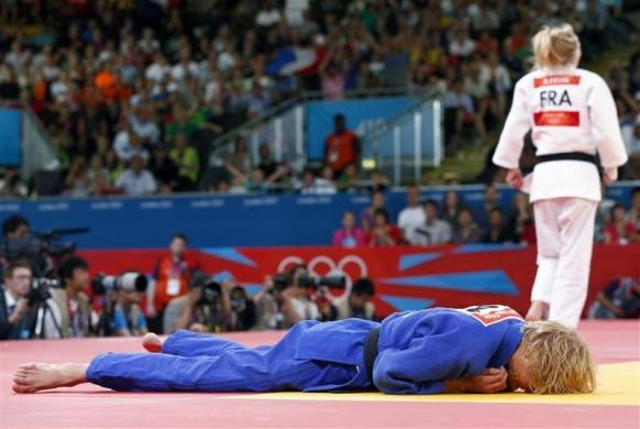 Austria's Sabrina Filzmoser (blue) lies on the mat after losing to France's Automne Pavia in their women's -57kg quarter-final judo match at the London 2012 Olympic Games July 30, 2012.   REUTERS/Darren Staples