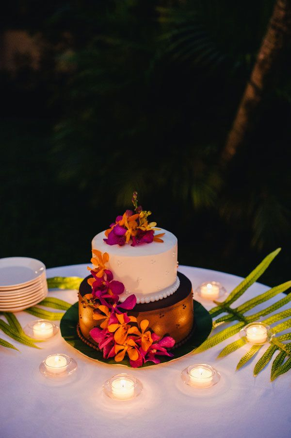 Small chocolate and vanilla wedding cake decorated with tropical flowers for wedding in Hawaii. See details of this relaxing and intimate Maui #wedding here: http://www.mywedding.com/articles/kristen-jasons-relaxed-kauai-hi-real-wedding-by-lydia-jane-photography/