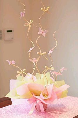 Table centerpiece. Wrap a pot in tissue paper and use the swirly twigs to come out of it. with bows and butterflies.