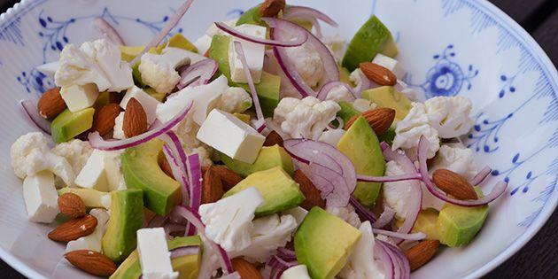 Dejlig frisk blomkålssalat med frisk blomkål, blød avocado, sprøde ristede mandler, cremet feta og tynde skiver rødløg.