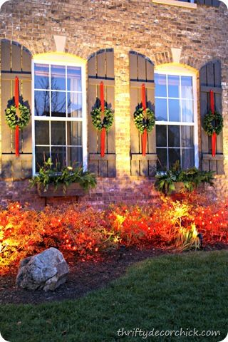 traditional outdoor holiday decor. Love hanging the wreath on the shutter.