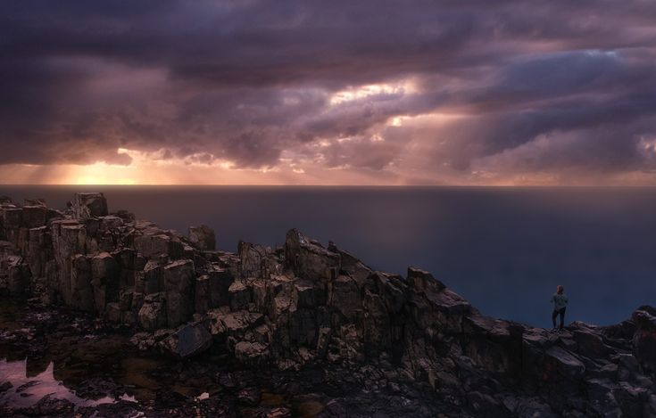 Standing tall on the rock pillars of Bombo Quarry as Sunrise breaks through the stormy sky. DJI Spark Drone Photography.