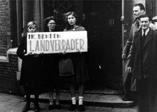 "Collaborators picked up from their homes forced to carry a sign reading ""I'm a traitor""."