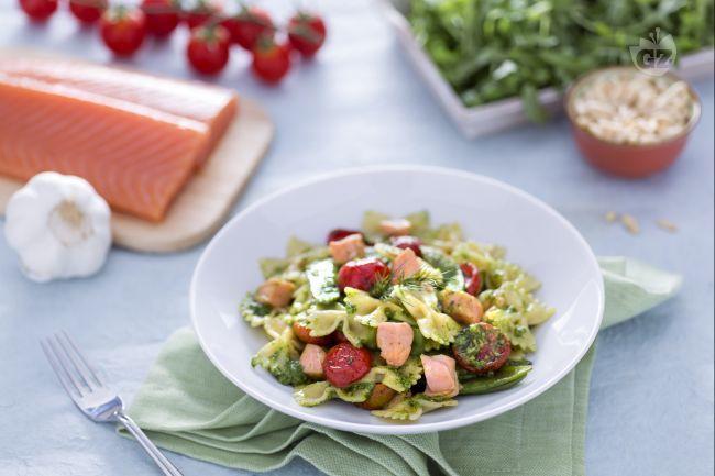 Le farfalle al salmone, taccole e pomodorini confit con pesto di rucola sono un primo piatto gustoso con un ricco condimento di pesce e verdure.