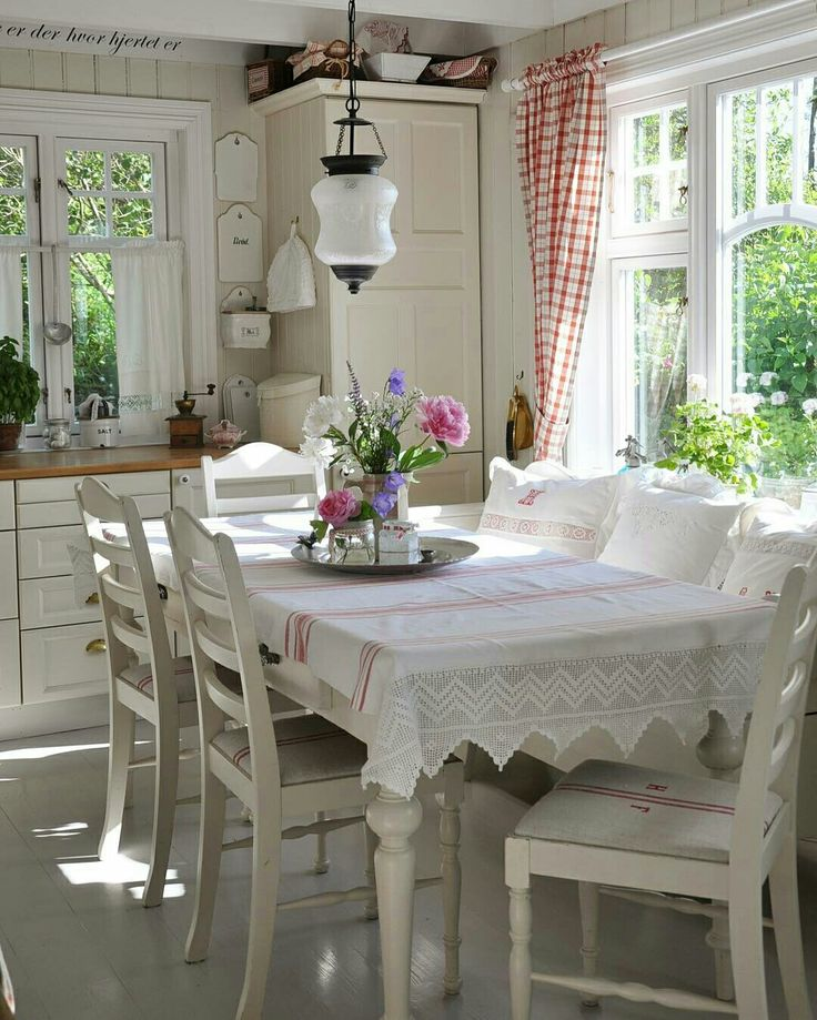 What an adorable white and cream kitchen with paneled walls So cozy! And love the lace edge on that cute white table cloth