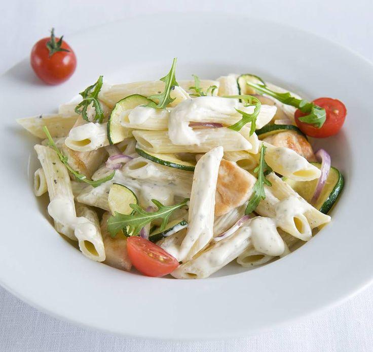 Dit recept is voor: 4 personen Aantal kcal: 520 p.p.  Zo maak je het! Kook de penne in weinig water met zout beetgaar.  Verhit in een koekenpan de olijfolie en bak de kipfilet 6 min. Bak de ui en courgette 4-5 min. mee.  Giet de pasta af en vang een kopje kookvocht op. Roer de Philadelphia tomaat & pesto light met ca. 75 ml kookvocht tot een romige saus.  Meng de pasta met de roomsaus door de kip. Schep er de rucola door en breng op smaak met zout en peper.  Verdeel de pasta over 4 diepe…