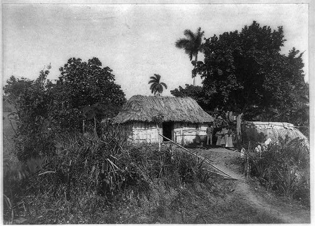 A Cuban house, countryside / Campo Florido (Family standing outside of thatched roof house.) // circa 1897 // Library of Congress Online Catalog
