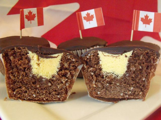 "Nanaimo Bar Cupcakes C & C Cakery: ""Yes, it may not seem like much - but the taste. You bite into one of these puppies, and you'll be singing O Canada! even if you don't know the words. Our special chocolate graham coconut cake was specially developed to remind you of that famous bar, while the vanilla custard filling and bittersweet chocolate ganache comes straight from the original recipe."" {will have to make these for our Canada Day Celebrati"