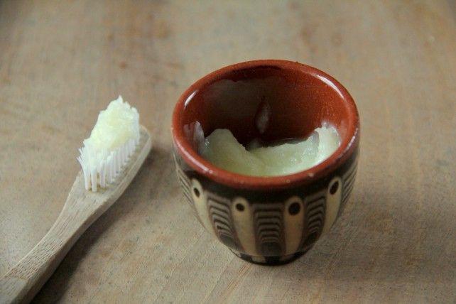Foto von einer Schale mit Kokoszahnpasta und einer Zahnbürste mit Zahnpasta drauf.