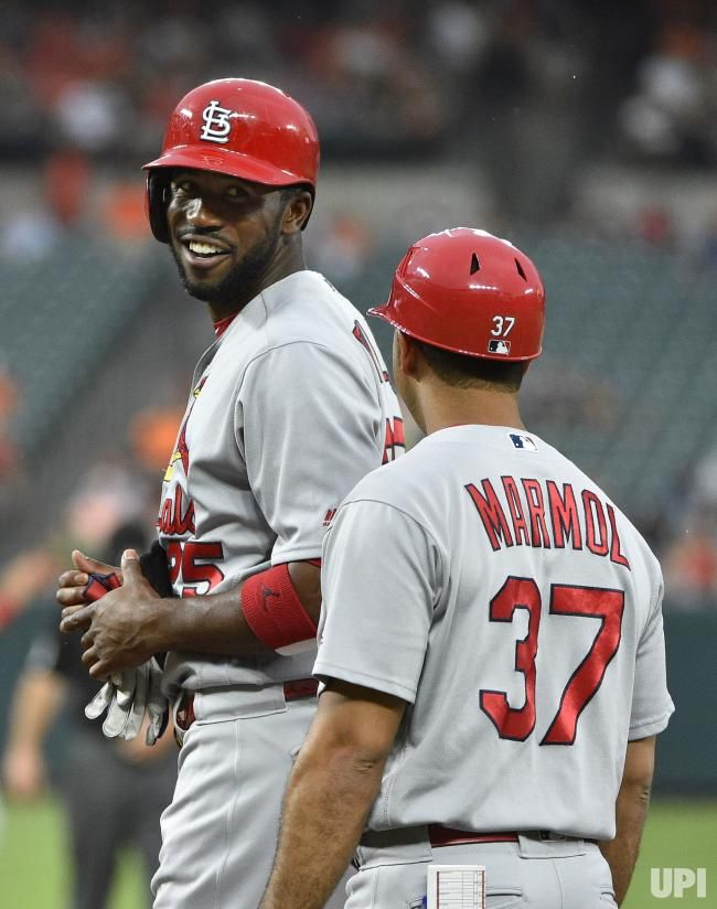 St. Louis Cardinals designated hitter Dexter Fowler (L) smiles after a base on balls scored a run against the Baltimore Orioles during the…