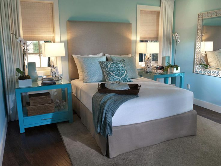 This robin egg blue bedroom is a tranquil space with beige accents and soft accent lighting. Oversized nightstands, an upholstered headboard, layered window treatments and impeccable accessories elevate the design of the room.