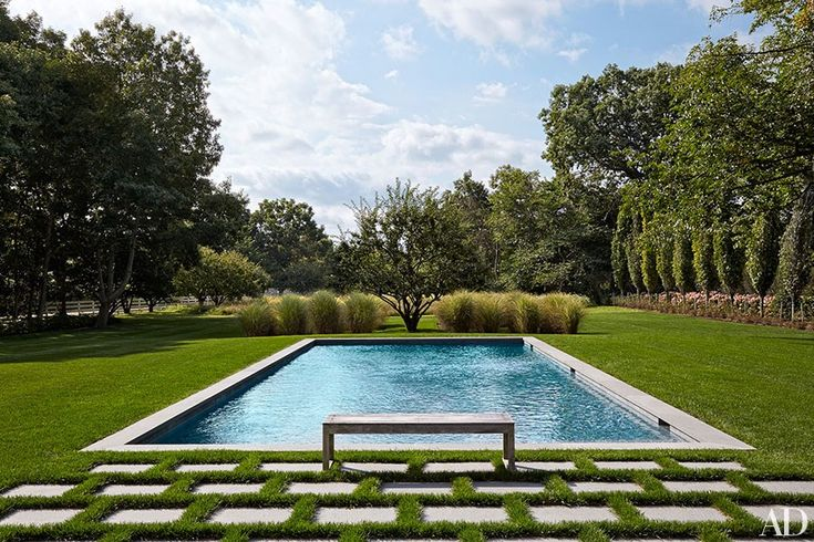 A Barlow Tyrie bench punctuates the pool area, which features bluestone coping | archdigest.com
