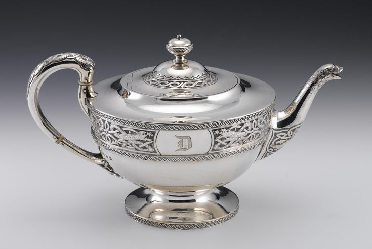Silver teapot with deep band of chased Celtic style interlace comprising intertwined gripping beasts enclosing a plain panel engraved with a gothic D, the spout terminating in an animal head, part of a teaset in the Celtic Festival style: Scottish, Glasgow, Edwards and Sons, 1917