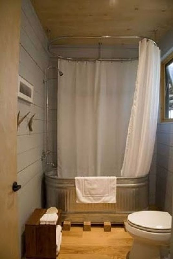 Water trough tub -- great thing is the doubled-up all-around shower curtain allows the wood walls all around.