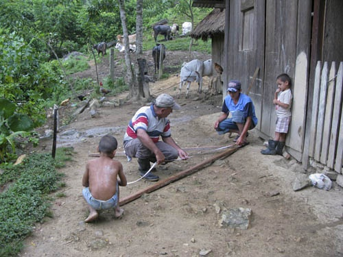 The whole family pitching in to help build an A-frame. With this brilliantly simple piece of technology they can measure the gradient of their steeply sloping fields and plant their Inga alleys along the contours to protect the soil from erosion.