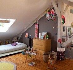 Une chambre d'enfant sous les combles qui joue les contrastes de bois naturels et peints.