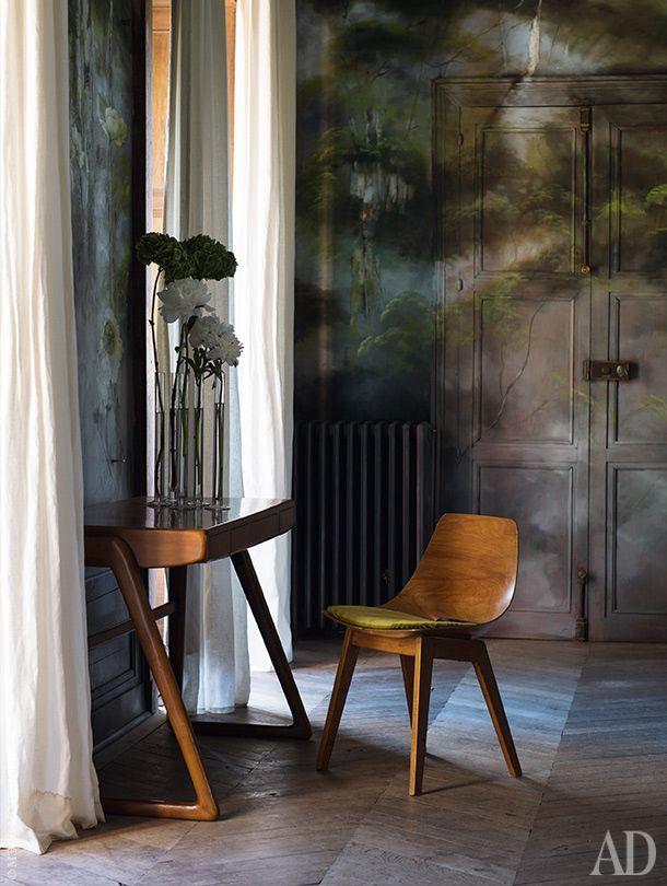 Фрагмент большой гостиной на первом этаже замка. Роспись покрывает не только стены комнаты, но и филенчатые двери. Стол и стул подокном — винтажные.