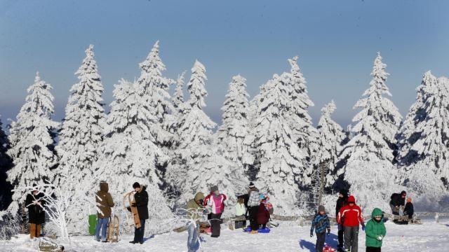 Pohon-pohon diselimuti salju sementara orang-orang berseluncur atau berjalan di puncak gunung Feldberg dekat Frankfurt, Jerman.