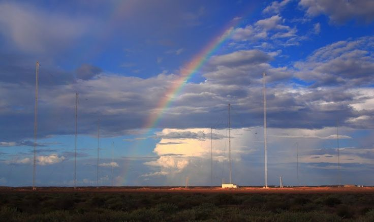 Thunderstorm lightshow.An almost invisible fall of drizzle from thunderstorm clouds creates a rainbow over the ex-U.S. Navy VLF communications towers at the north end of North West Cape HAARP