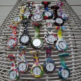 """Een modern VERPLEEGSTERSHORLOGE dat ideaal is als je (tijdelijk) geen horloge om je pols kan dragen.Met de metalen clip is het klokje gemakkelijke te bevestigen aan je uniform of zakje zonder dat deze beschadigd door een stekertje. Het uurwerk hangt ondersteboven zodat je van bovenaf kunt zien hoe laat het is maar is te draaien zodat het ook """"normaal"""" kan hangen.Om het klokje zit een flexibele silicone behuizing die eenvoudig te reinigen is en tegen een stootje kan."""
