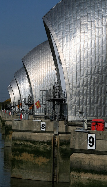 Thames Barrier  London   by ruthhallam, via Flickr - another example of the OIL CANNING effect on light gauge metal panel sheets that became part of the building facade design. Cheers - YL