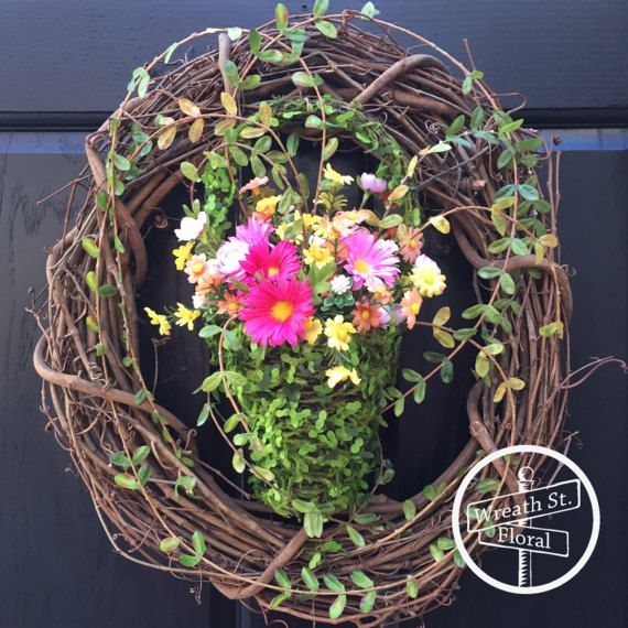Dress your door with this charming wildflower wreath. This wreath features a moss basket, petite leaf vine and wildflowers in shades of pink, yellow, orange and moss green. Tip to tip measurement is 18W 19L 6D Created on a 18 inch grapevine wreath Item M1048 READY TO SHIP  Note: Florals placed outdoors will weather over time from exposure to the elements.