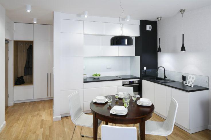 Kuchnię w bloku urządzono w bieli. Jadalnię usytuowano na granicy z salonem. Organizuje ją okrągły zabytkowy stolik, odziedziczony po babcie. Projekt Ewelina Para. Fot. Bartosz Jarosz.