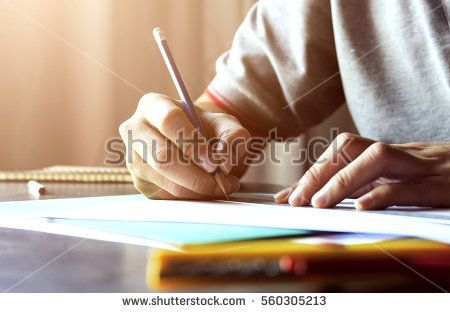 hand writing in notebook on wood table with warm fall colors and soft-focus in the background. over sunlight