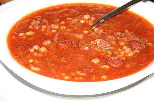 Густой фасолевый суп с капустой Ингредиенты: говяжий бульон (вода)4 литров белая мелкая фасоль1.5 стакан банка квашенной капусты1/2 литров колбаски чили150 гр. крупная морковь1 шт. крупная луковица1 шт. томатная паста3-4 ст. л. чеснок3-4 шт. растительное маслопо вкусу соль, перец, красная сладкая паприка, лавровый лист, сушенный укроп и петрушка