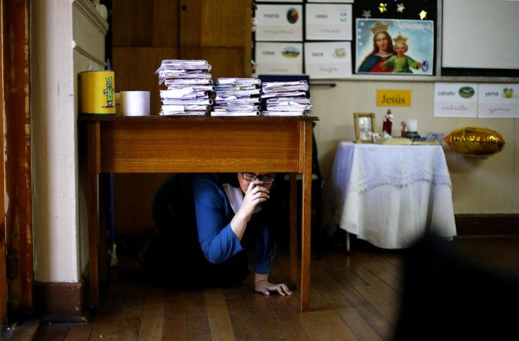 A teacher takes cover under her desk inside a school during an earthquake drill in Santiago, Chile. Around one million residents, including students, teachers and parents, took part on Thursday in a drill that simulated a fictitious earthquake of a magnitude of 8.8 on the Richter scale.