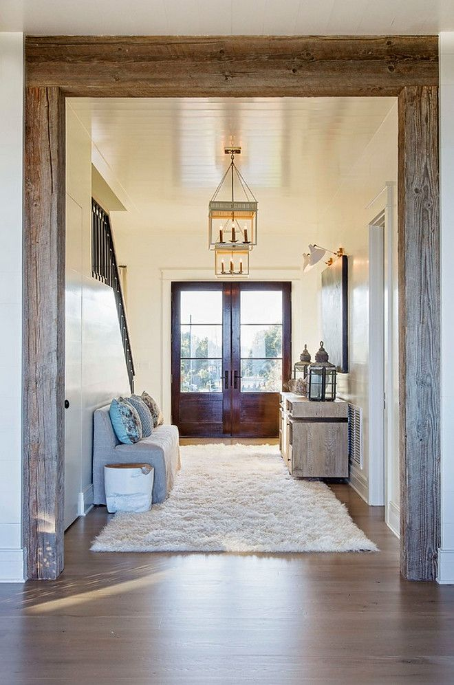 A reclaimed beamed doorway opens to main living areas of this beach house.