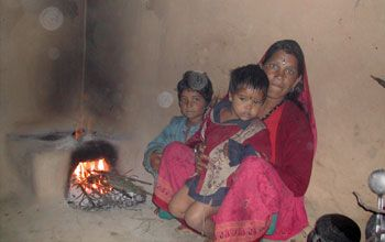 a Indian woman and her two children with a dung or wood fuel cooking stove.