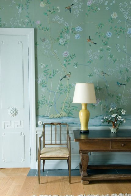 The beautiful DeGournay wallpaper is offset by a yellow table lamp. #AntiqueChair #AntiqueDesk #BirdWallpaper #DeGournay #Flagstones #FloralWallpaper #GreekPattern #Meander #SlateFlooring #StoneAndWoodenFlooring #GreenWallpaper #WoodenFloor #YellowLamp