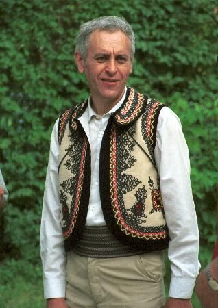 Romanian costume Oltenia  White fabric waistcoat called vestă made of aba and decorated with black braid (şabace) , forms part of portul schileresc, which became fashionable in late 19th century. Striped brâu (fabric belt).  Photo taken at Astra Museum, Sibiu, August 1998