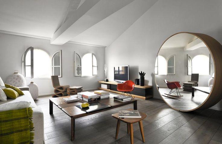 Un attico sul porto vecchio di Marsiglia. Il mobile TV è su disegno di Francois Champsaur e realizzato in legno di rovere naturale, che riprende lo stesso materiale della cornice dello specchio. Sempre di rovere anche il pavimento, uguale per tutta la casa, in una tonalità di grigio.
