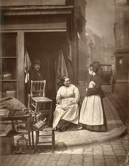 "Old Furniture From 'Street Life in London', 1877, by John Thomson and Adolphe Smith:    ""At the corner of Church Lane, Holborn, there was a second-hand furniture dealer, whose business was a cross between that of a shop and a street stall. The dealer was never satisfied unless the weather allowed him to disgorge nearly the whole of his stock into the middle of the street ... It was a celebrated resort for tramps and costers of every description."""